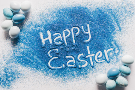 top view of happy easter sign made of blue sand with painted eggs