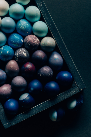 top view of colored painted easter eggs in wooden box