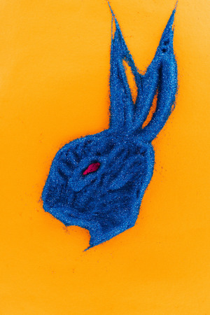 top view of easter bunny made of blue sand