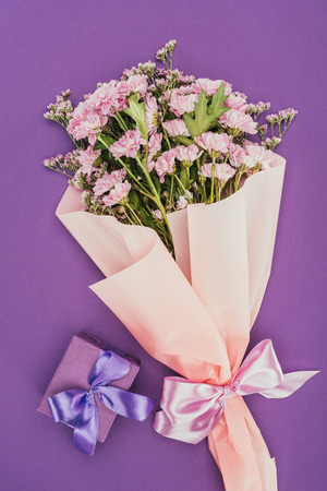 bouquet of beautiful pink flowers and gift box on violet 스톡 콘텐츠