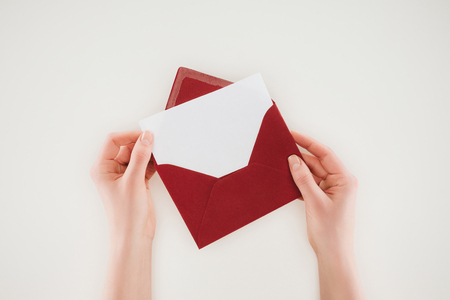 cropped shot of woman opening red envelope with blank paper isolated on white