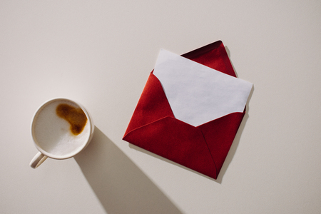 top view of red envelope with blank paper and cup of coffee Zdjęcie Seryjne
