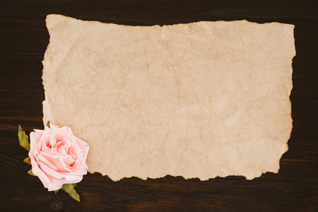 top view of blank aged paper and rose flower on wooden table