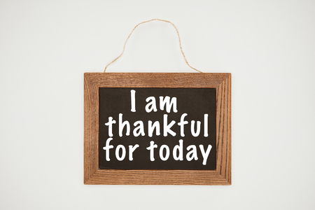 i am thankful today lettering on chalkboard with wooden frame and thread isolated on white Stock Photo