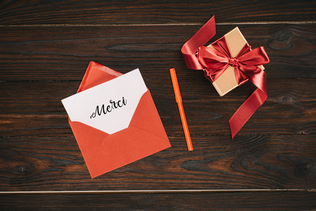 top view of red envelope with merci lettering on paper and gift box on wooden table Stock Photo