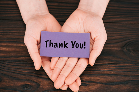 cropped shot of woman holding purple paper with thank you lettering over wooden table