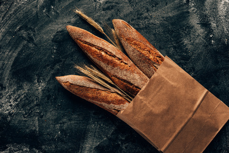 top view of arranged french baguettes in paper bag and wheat on dark tabletop with flour Standard-Bild