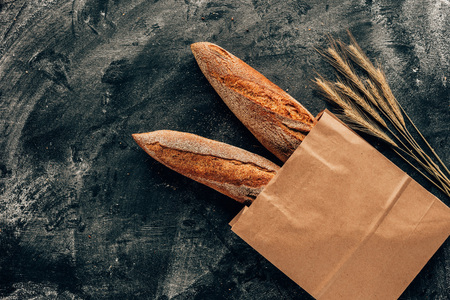 top view of arranged french baguettes in paper bag and wheat on dark tabletop with flour Banco de Imagens