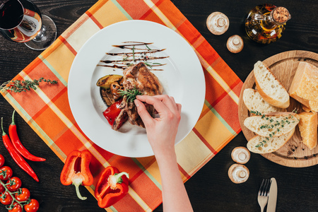 cropped image of woman putting rosemary twig on grilled chicken