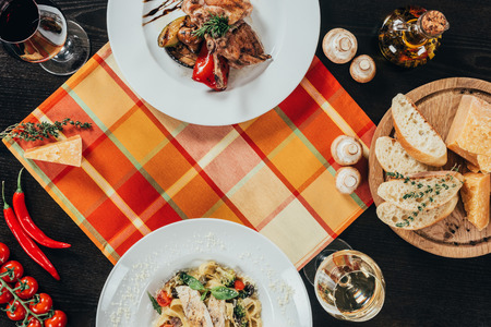 top view of pasta with pike perch fillet and chicken with grilled vegetables on table Standard-Bild