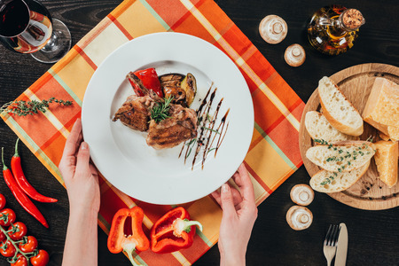 cropped image of woman putting plate with grilled chicken on table Imagens