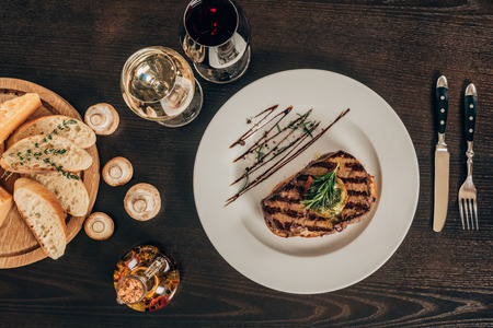 top view of beef steak, baguette and wine on table Standard-Bild