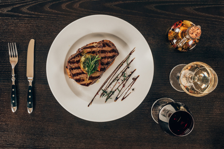 top view of beef steak on plate and glasses with wine on table
