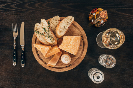 top view of parmesan cheese with baguette slices and mushroom on wooden board