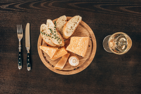 top view of parmesan cheese with baguette slices on wooden board Standard-Bild