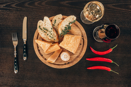 top view of parmesan cheese with baguette slices on wooden board, chili peppers and wine on table Standard-Bild