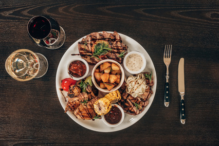 top view of plate with beef steaks, chicken wings and wine on wooden table