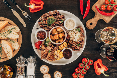 top view of plate with beef steaks, grilled vegetables and wine on table Standard-Bild