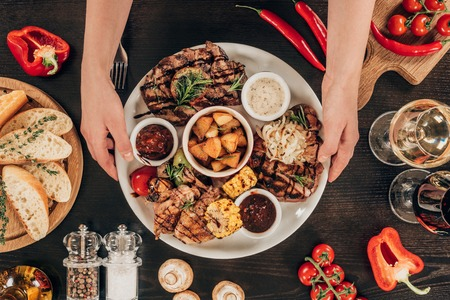cropped image of woman putting plate with beef steaks, chicken wings and grilled vegetables on table