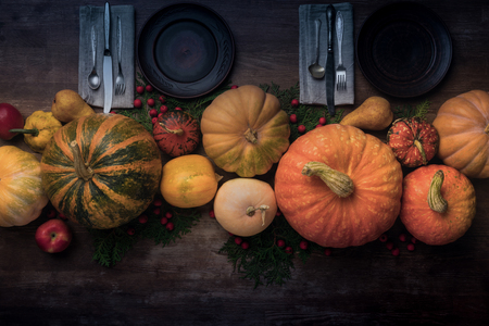 Top view of wooden plates and cultery with different autumnal vegetables and fruits in the center of wooden table