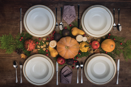 Top view of four plates with cutlery and autumnal vegetables on wooden table