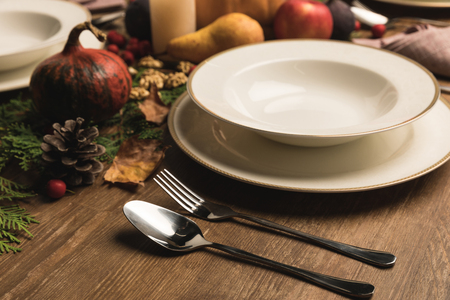 Plate and cutlery on served table with various autumnal vegetables and fruits