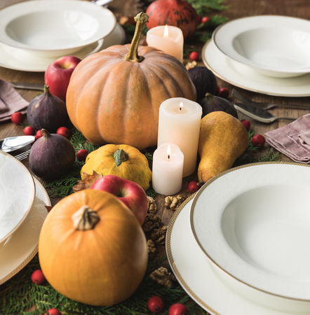 Plates and cultery with different autumnal vegetables and fruits on wooden table Stock Photo