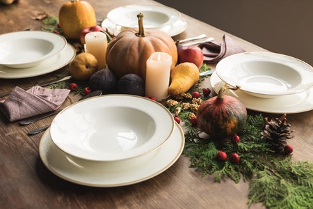 Plates and cultery with various autumnal vegetables and fruits on wooden table Stock Photo