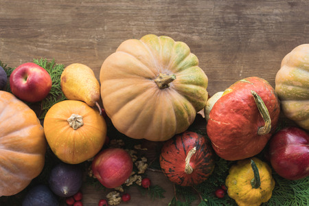 Top view of composition with various autumnal vegetables and fruits on wooden table