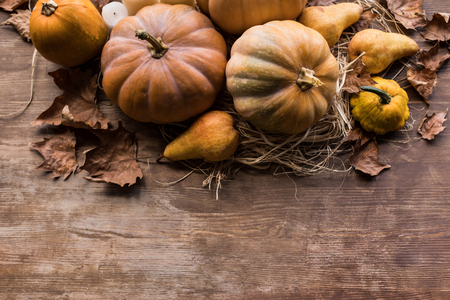 Top view of composition with pumpkins, pears and leaves on wooden table