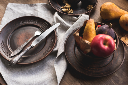 empty plate with fork and knife and ripe autumn fruits on wooden table  Stock Photo
