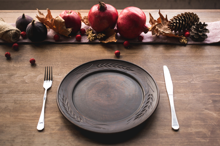 close-up view of empty plate with fork and knife, pine cones and ripe fresh fruits on table   Stock Photo