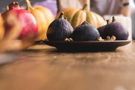 close-up view of ripe healthy figs on plate on wooden table