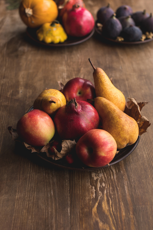 close-up view of ripe autumn fruits and dry leaves on rustic wooden table