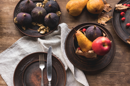 top view of ripe seasonal fruits on plates on wooden table