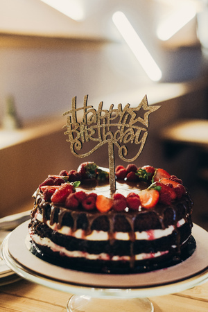 Happy Birthday sign on chocolate cake with fruits