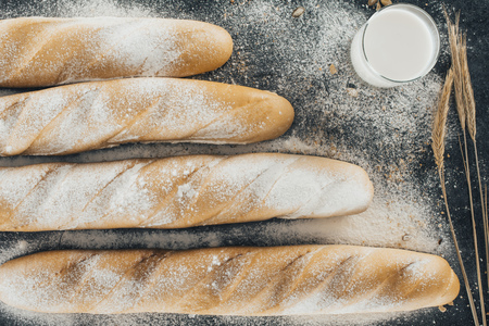 top view of fresh baguettes, milk in glass and spikelets on black