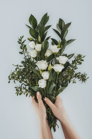 cropped image of female hands holding bouquet with eustoma flowers isolated on grey