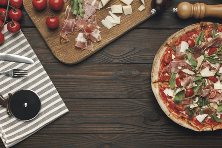 flat lay with arranged italian pizza, cutlery and various ingredients on wooden surface Stok Fotoğraf