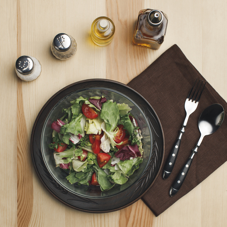 flat lay with arranged salad in bowl, spices and bottles of oil on wooden surface