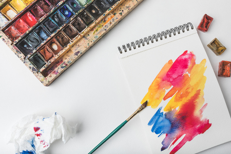 top view of watercolor paints and paintbrush at designer workplace