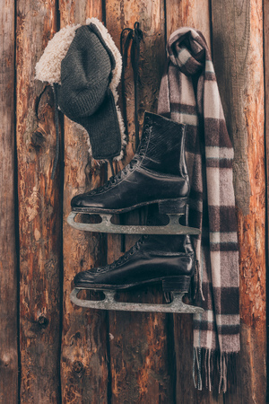 hat with ear flaps with scarf and black skates hanging on wooden wall