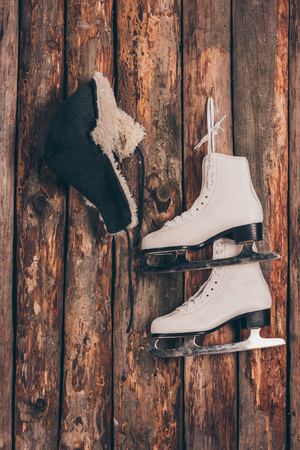 hat with ear flaps and pair of skates hanging on wooden wall Stock Photo
