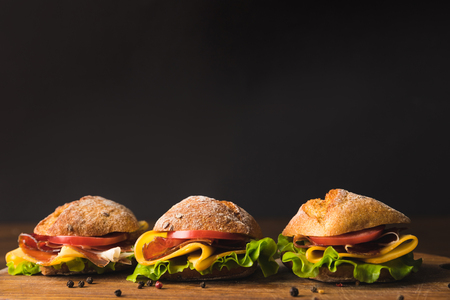 sandwiches with cheese and vegetables on wooden board with scattered pepper Banco de Imagens