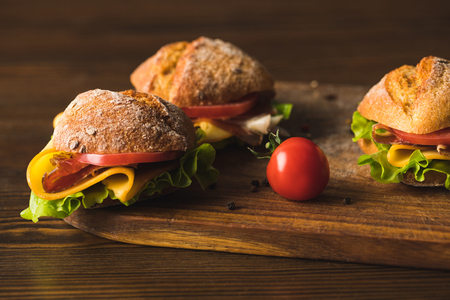 sandwiches with cheese and cherry tomato on cutting board Stock Photo