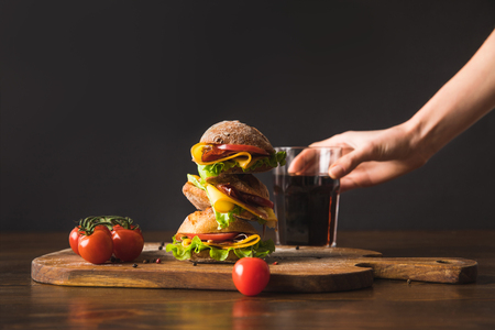 cropped image of woman taking glass of cola from table with big tasty sandwich