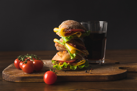 big sandwich with cheese, cherry tomatoes and glass of cola on cutting board