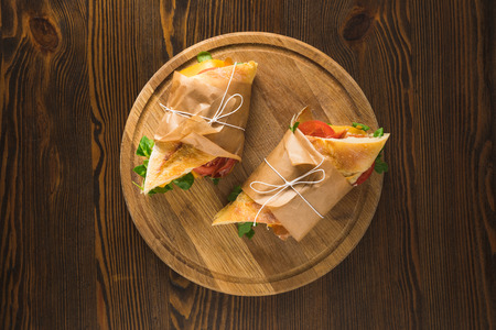 top view of two delicious panini on wooden round board