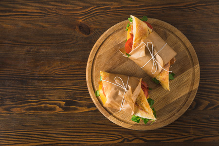 top view of two delicious panini on cutting board on wooden table Banco de Imagens