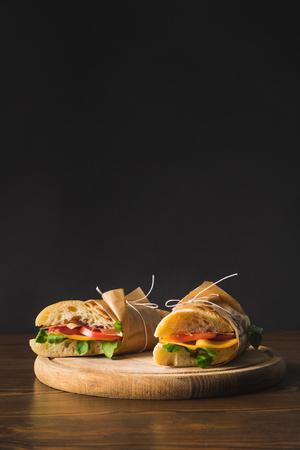 Deux sandwichs appétissants cuits avec des légumes sur une planche à découper Banque d'images - 98683181